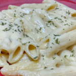 The creamy pasta sauce on the penne pasta on a plate, dusted with parsley and ready to eat.