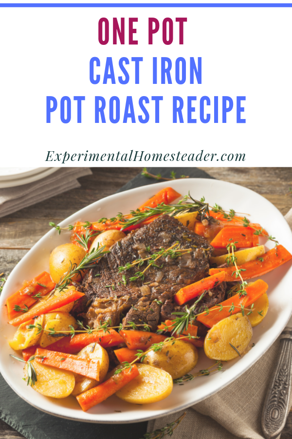 Pot roast with potatoes and carrots garnished with thyme and rosemary on a platter.