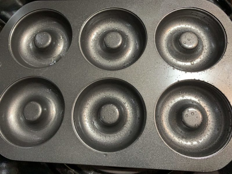 The lightly greased donut pan.