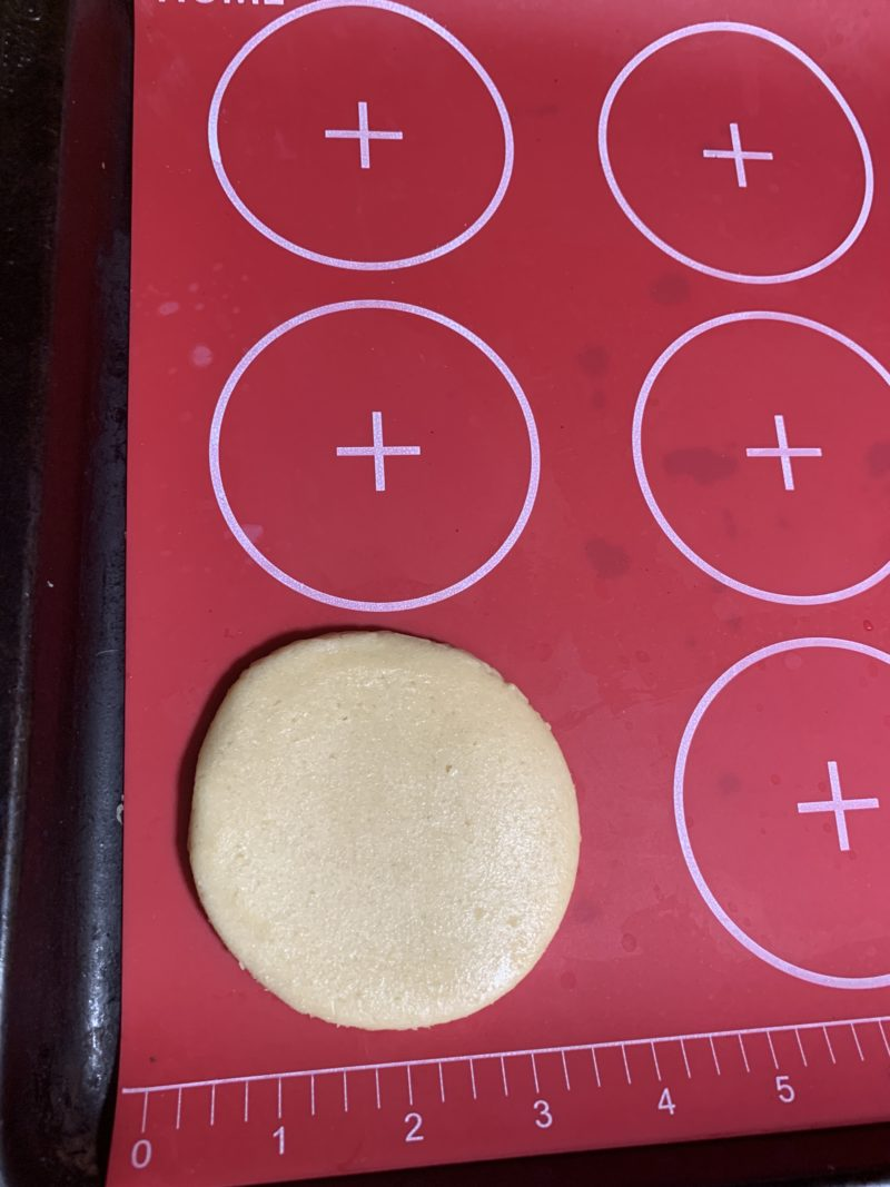 The shaped sugar cookie on a silicone mat laying on a cookie sheet.