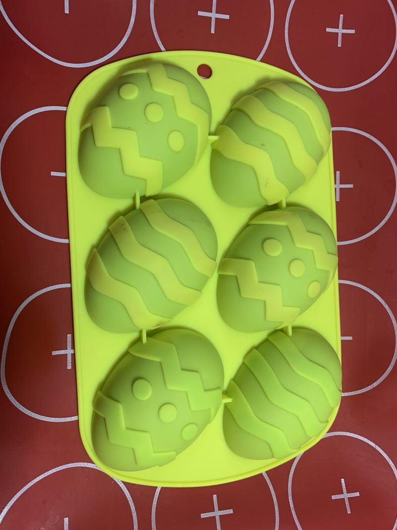 The silicone mat under the silicone mold filled with the chocolate creme filled eggs.