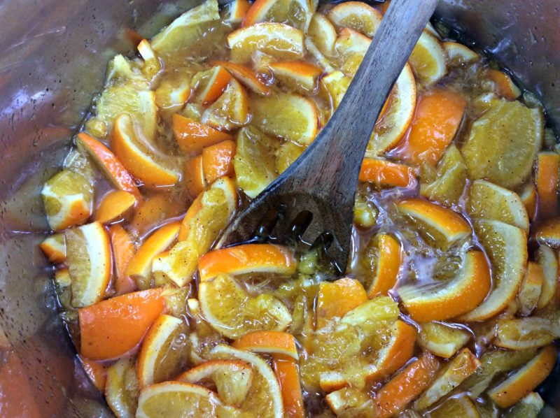 A wooden spoon being used to stir the clementine's in the Instant Pot.